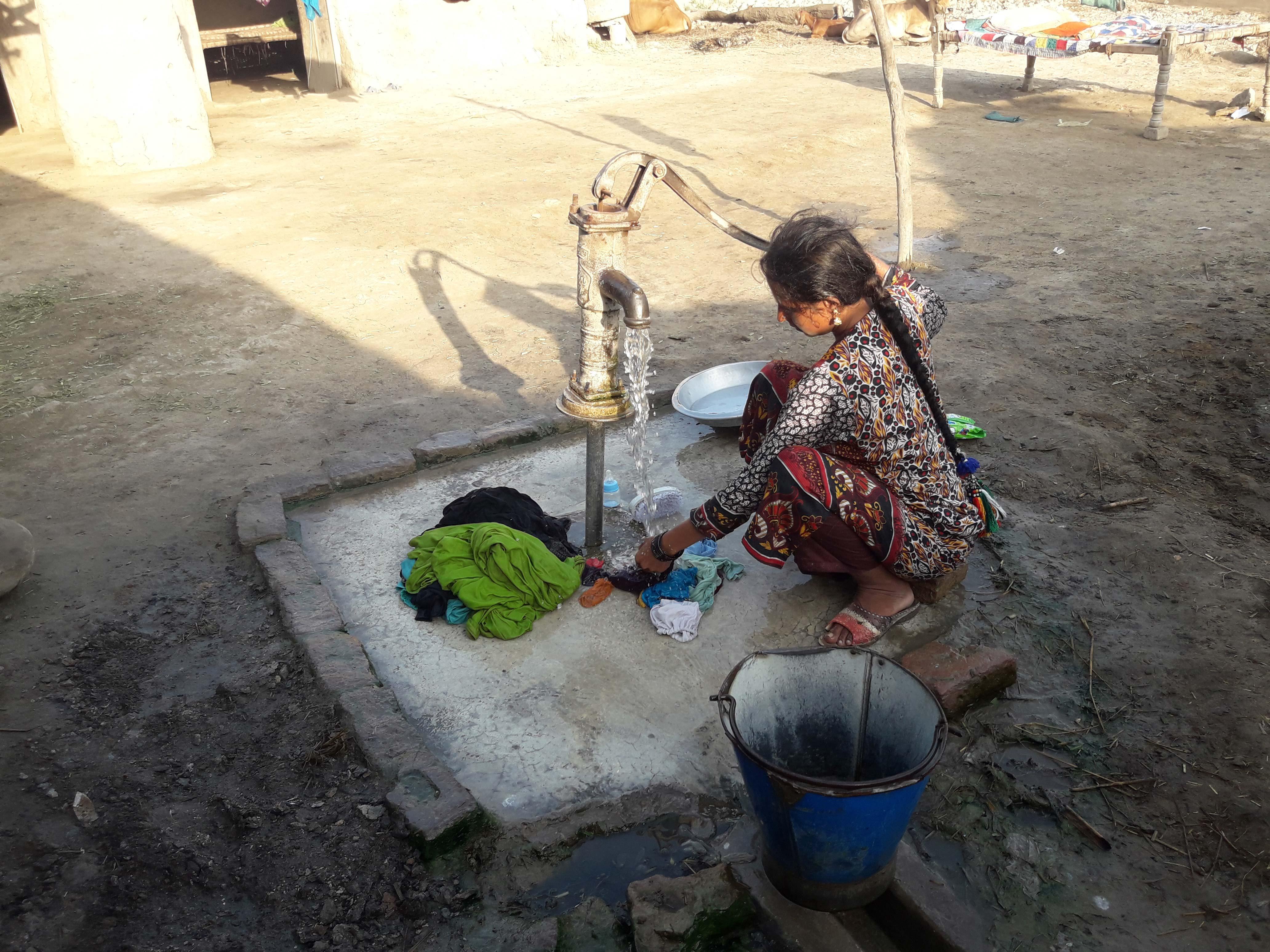 A woman in Dasti Village washing clothes under a hand-pump